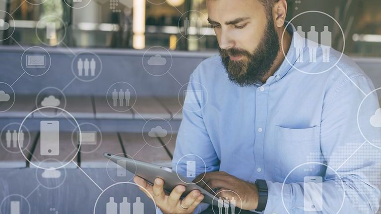 Young bearded hipster man sits and uses digital tablet. In foreground are virtual icons with people, digital gadgets.